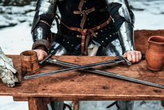 Man at the table with two swords stock images
