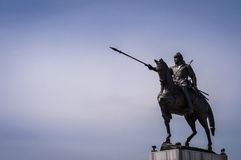 Male Warrior Statue With Horse. Bronze statue of a male figure riding a horse with bow on the shoulder and spear on hand with open blue sky on the background Stock Photo