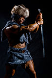 Male warrior with a sword. In the form of a barbarian on a black background Royalty Free Stock Photography