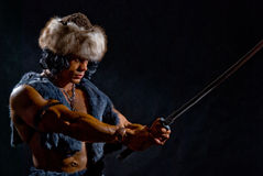 Male warrior with a sword in the form. Of a barbarian on a black background Stock Image
