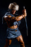Male warrior with a sword in the form of a barbarian. On a black background Stock Photo