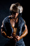 Male warrior with a sword in the form of a barbarian. On a black background Royalty Free Stock Images