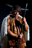 Male warrior with a sword in a fur cape. On a black background Royalty Free Stock Photos