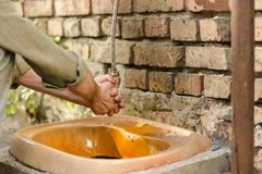 Male washing hands in the street yard. Hygiene of homeless man Royalty Free Stock Photography