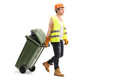 Male waste collector dragging a trash can Stock Images