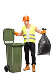 Male waste collector picking up trash. Full length portrait of a male waste collector picking up a bag from a trash can isolated on white background Stock Photography