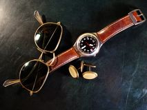 Male watch, cuff buttons and sunglasses. Laying on dark green surface of leather top desk. Male concept stock photography