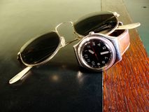 Male watch and a sunglasses on leather top desk royalty free stock photography