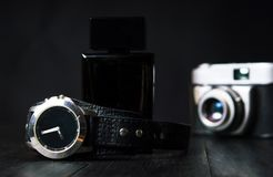 Male watch, vintage camera and perfume. On dark background Royalty Free Stock Images