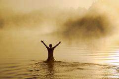 Male in water. Silhouette of a male with raised arms in the water Stock Image