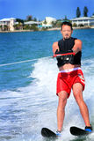 Male Water Skier. A man water skiing wearing red trunks and a black life vest on a sunny day in front of some luxury waterfront homes Royalty Free Stock Photos