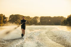 Male water skiing behind a boat on lake. Man riding wakeboard on wave of motorboat. Male water skiing behind a boat on lake Royalty Free Stock Photos