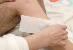 Male waxing. Beautician while making a male waxing with wax strips Royalty Free Stock Photos