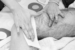 Male waxing in Black and white. Beautician while making a male waxing with wax strips Stock Photography