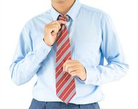 Male wearing blue shirt and red tie with clipping path. Close up, Male wearing blue shirt and red tie, he tighten the tie knot with clipping path Royalty Free Stock Photography