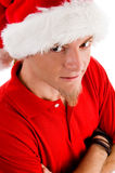 Male wearing christmas hat looking at camera. Against white background Royalty Free Stock Photography