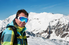 Male wearing goggles and ski jacket smiling Stock Images