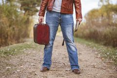 Male wearing a leather jacket and jeans standing on a pathway holding old suitcase and bible
