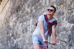 Male Wearing Sunglasses With Bike. Handsome young hipster man wearing sunglasses with bicycle in the street on sunny day Royalty Free Stock Photography