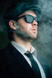 Male wearing sunglasses and a leather cap in the smoke. Fashionable male wearing sunglasses and a leather cap in the smoke Royalty Free Stock Photo