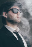 Male wearing sunglasses and a leather cap in the smoke. Fashionable male wearing sunglasses and a leather cap in the smoke Stock Photo