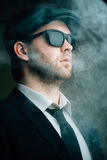 Male wearing sunglasses and a leather cap in the smoke. Fashionable male wearing sunglasses and a leather cap in the smoke Stock Photos