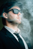 Male wearing sunglasses and a leather cap in the smoke. Fashionable male wearing sunglasses and a leather cap in the smoke Stock Photography