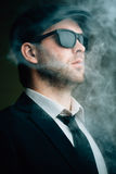 Male wearing sunglasses and a leather cap in the smoke. Fashionable male wearing sunglasses and a leather cap in the smoke Royalty Free Stock Photos