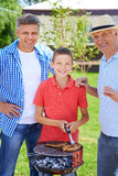 Male weekend. Grandpa, father and boy grilling sausages Stock Photography