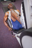 Male weightlifter doing leg presses in gym Stock Photography