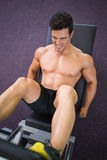 Male weightlifter doing leg presses in gym Stock Images
