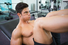Male weightlifter doing leg presses in gym Stock Photo