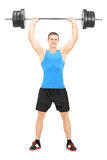 Male weightlifter holding a barbell. Full length portrait of a male weightlifter holding a barbell isolated on white background Stock Image