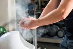 Male weightlifter processes hands talcum powder. Against sliding Royalty Free Stock Image