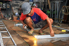 Male welder/fabricator welding metalwork in workshop. Kuta/Bali - September 13, 2016: Male welder/fabricator welding metalwork in workshop Royalty Free Stock Photography