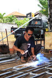 Male welder/fabricator welding metalwork in workshop. Kuta/Bali - September 13, 2016: Male welder/fabricator welding metalwork in workshop Stock Images