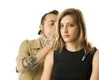 Male whispering to female. Caucasian mid-adult man whispering into ear of teen female Stock Images