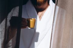 Male in white bathrobe with coffee mug in hand. Male is standing by window in white bathrobe with coffee mug in hand stock image