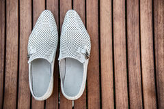 Male white shoes over the wooden table.  Royalty Free Stock Images