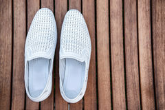 Male white shoes over the wooden table.  Stock Photos
