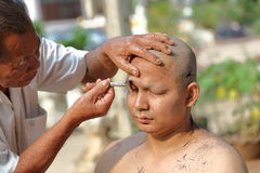 Male who will be monk shaving hair for be Ordained. NAKHON RATCHASIMA, THAILAND-APRIL 12: Male who will be monk shaving hair for be Ordained to new monk on April Stock Photography