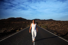 Male on the wide road. Lanzarote, Canary Islands, Spain. Male in white clothes on the road Stock Image