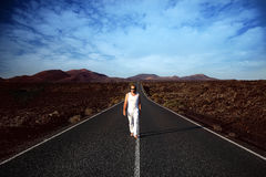 Male on the wide road. Lanzarote, Canary Islands, Spain. Male in white clothes on the road Royalty Free Stock Images
