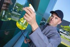 Male window cleaner spraying product. Window Stock Photo