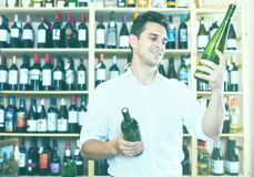 Male wine expert holding wine bottles in winery section Stock Images