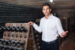 Male wine maker showing bottles on winery Royalty Free Stock Images