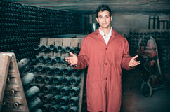 Male wine maker showing bottles on winery Stock Photos