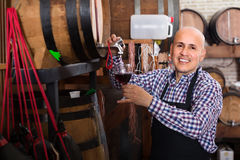 Male wine maker taking wine from wood Royalty Free Stock Photos