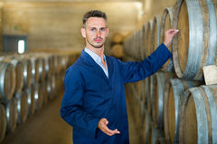 Male wine maker working in winery cellar Stock Photos