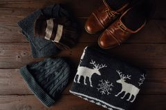 Male winter clothing on a brown wooden background. Male winter style on a brown wooden background. Winter brown shoes, grey sweater with deer, grey knitted Stock Photos
